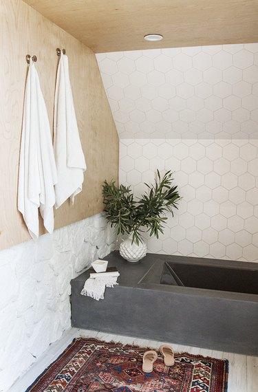 bathroom tile idea with white hexagonal tile on wall next to concrete tub