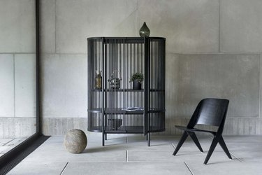 black chair near cabinet and concrete wall