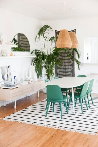 bohemian dining room idea with large potted plant and woven pendant lights above table with green chairs