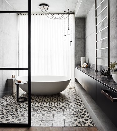 patterned bathroom tile idea on floor and freestanding tub with concrete walls and floor-to-ceiling window