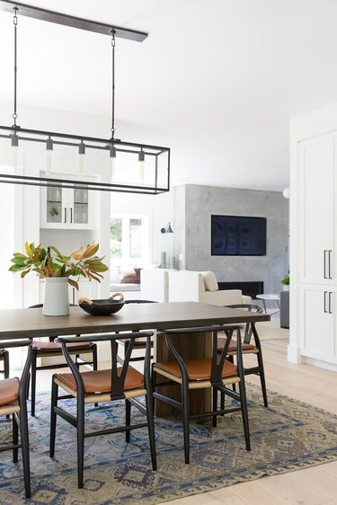 open concept dining room idea with wishbone chairs and rectangular chandelier that opens to living room and kitchen