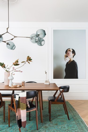modern dining room idea with statement lighting, teak chairs and large scale art