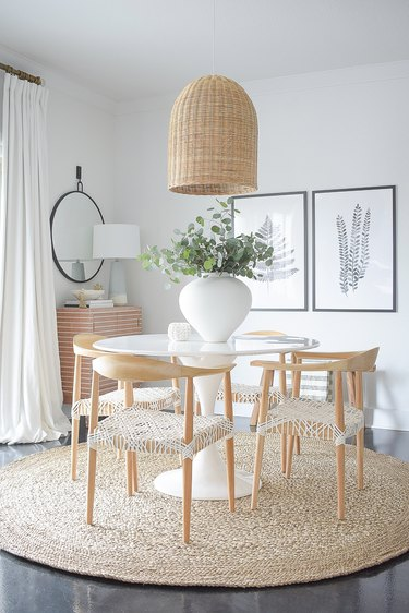 dining room lighting idea with woven bell pendant over round table with round rug