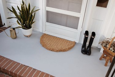 Rug, plant, boots and watering can on concrete porch painted gray