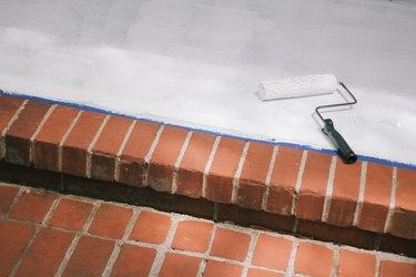 Rolling primer onto concrete porch