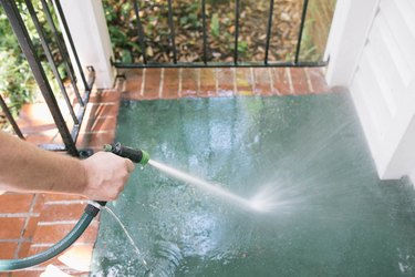 Rinsing concrete porch clean with water hose