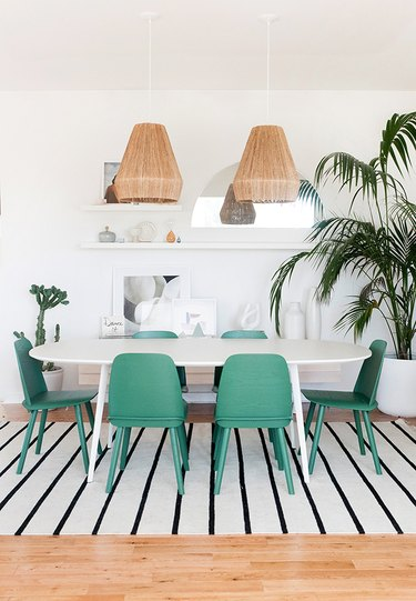 dining room lighting idea with woven jute pendants over oval table and green chairs