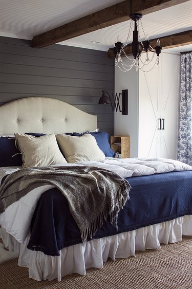 bedroom with gray shiplap walls and rustic wood ceiling beams