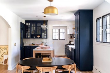 dining room lighting idea with brass pendant hanging over oval table near kitchen with blue cabinets