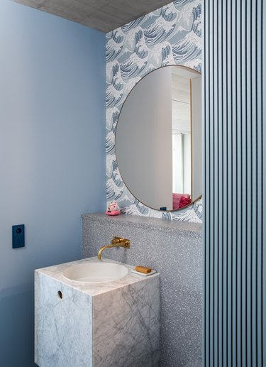 sky blue bathroom color  with mirror and wallpapered backsplash
