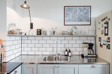 Scandinavian kitchen with stainless steel countertops and white subway tile backsplash