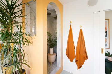 golden yellow bathroom color idea with accent wall and orange towels