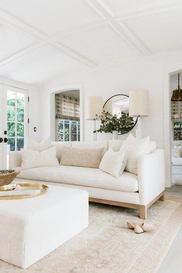white living room with plush sofa and ottoman