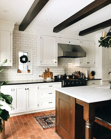 modern farmhouse kitchen with wood ceiling beams and brick flooring