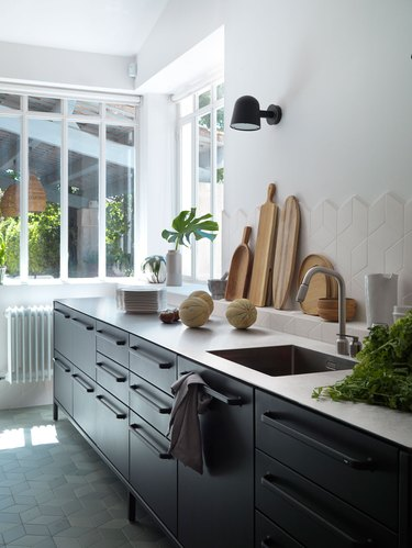 stainless steel kitchen countertops with black cabinets and white tile backsplash
