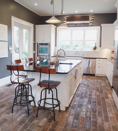 industrial kitchen with white cabinets and brick flooring