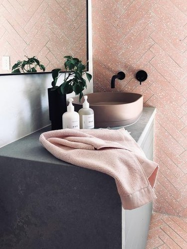 concrete bathroom countertop with vessel sink and pink wall and floor tile with wall-mounted faucet