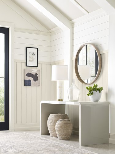 entryway space with a round mirror and white walls