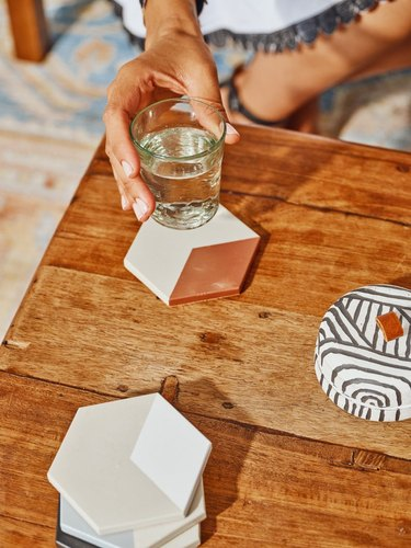 person holding glass over concrete hexagon coaster