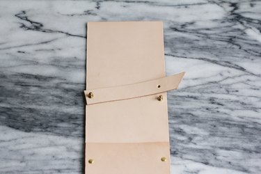 Brass stud screwbacks attached through holes on leather strip