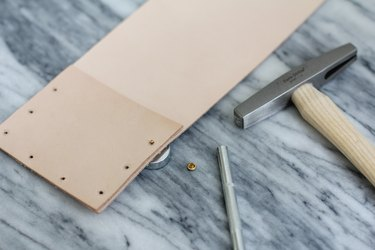 Placing base of rivet through hole