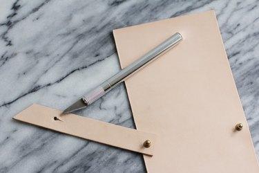 Cutting a slit through hole on leather strip
