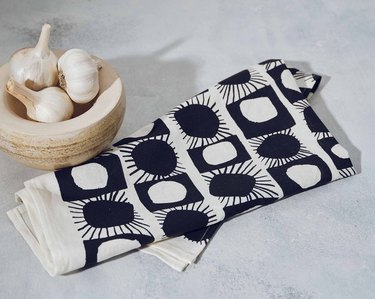 bowl with garlic near black and white tea towel