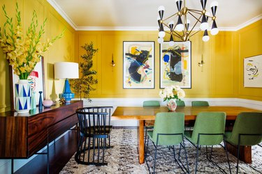 dining room lighting idea with chandelier over table and set of wall sconces around artwork