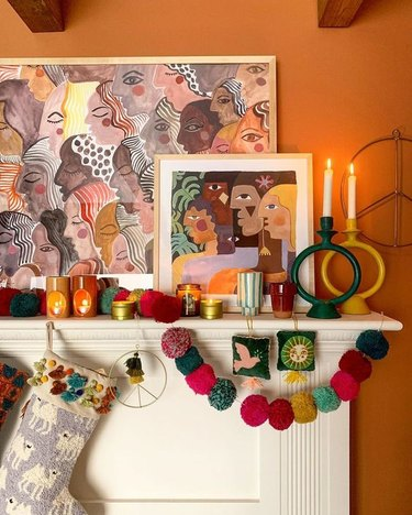 boho Christmas theme decor idea with stockings and garland hanging from mantel