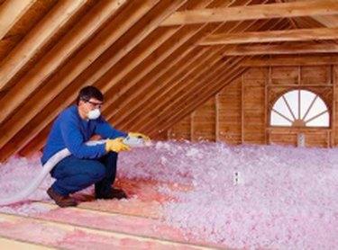 Blowing attic insulation.