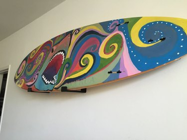 Surfboard hung on wall.