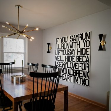 dining room lighting idea with chandelier over table and set of wall sconces next to artwork