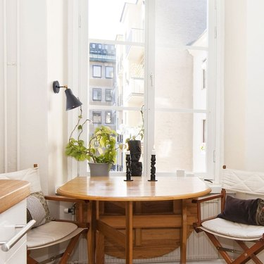 dining room lighting idea with adjustable wall sconce near window