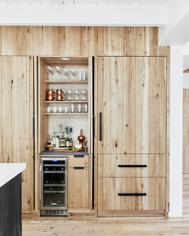 wood kitchen cabinet design with black hardware and matching wood flooring