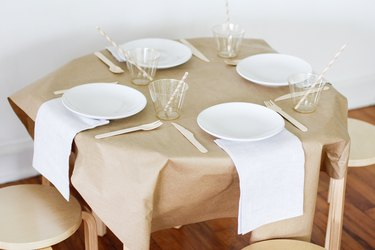 Kraft paper on table with plates, cups and utensils