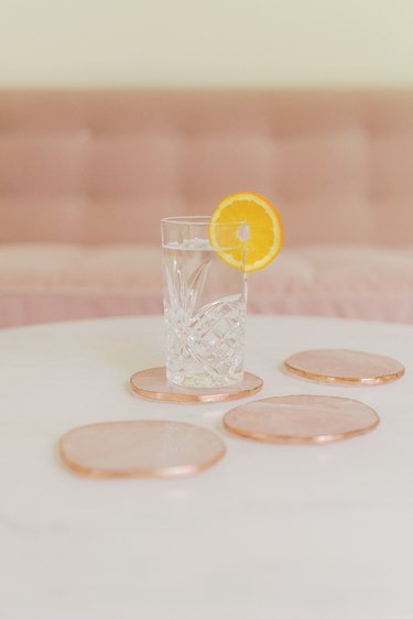 table with rose quartz coasters and glass with orange slice