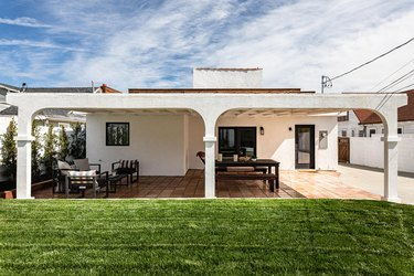 The backyard of a Spanish-style home; green grass in the yard and patio furniture underneath the covered patio