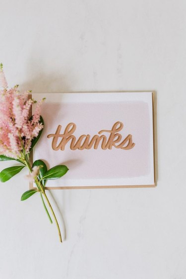 card that read thanks with flower nearby