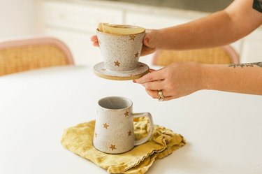 person holding stone pour over with mug underneath