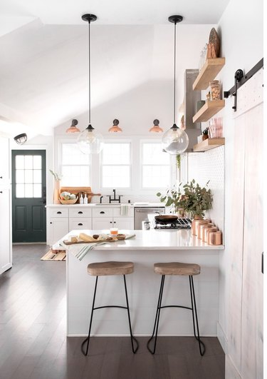 Small kitchen with island, bar stools, white cabinets, pendant lights.