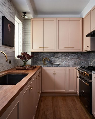 Kitchen with dusky pink cabinets and subway tile on walls with marble backsplash