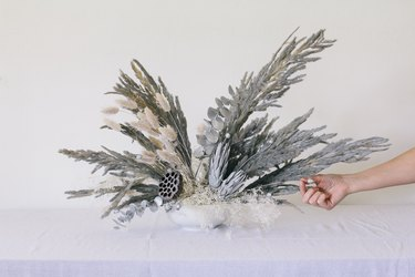 Placing dried centaurea pods into vase