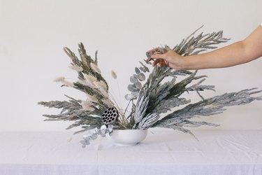 Placing eucalyptus into vase