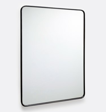 Large rounded rectangular mirror with thin aged bronze border that appears black