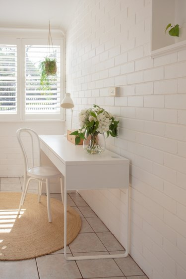 white home office idea with desk against brick wall
