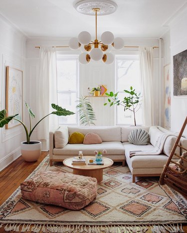 sunset-inspired white living room with midcentury chandelier and sectional sofa