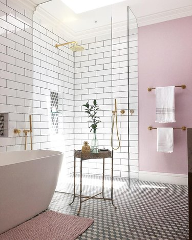 sunset-hued pink bathroom with subway tile on walls and freestanding tub