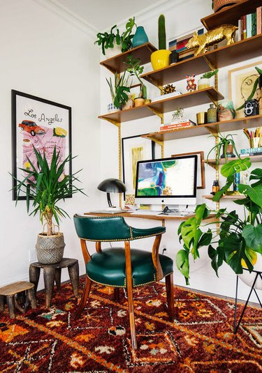 bohemian home office with green chair and red rug