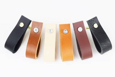 Six leather drawer pulls in varying shades of brown, black, and cream