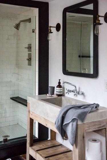 concrete bathroom sink on wood vanity in industrial bathroom